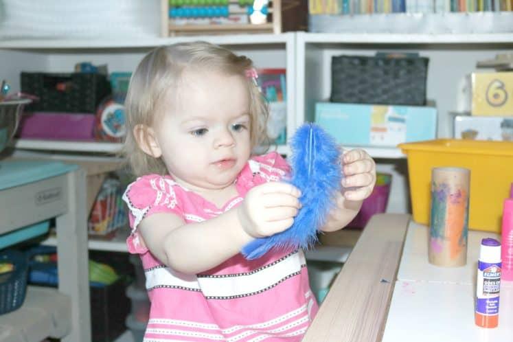 preschooler exploring blue feather