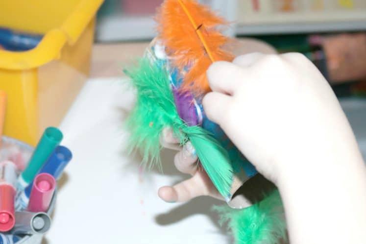 preschooler gluing feathers onto cardboard roll bird craft