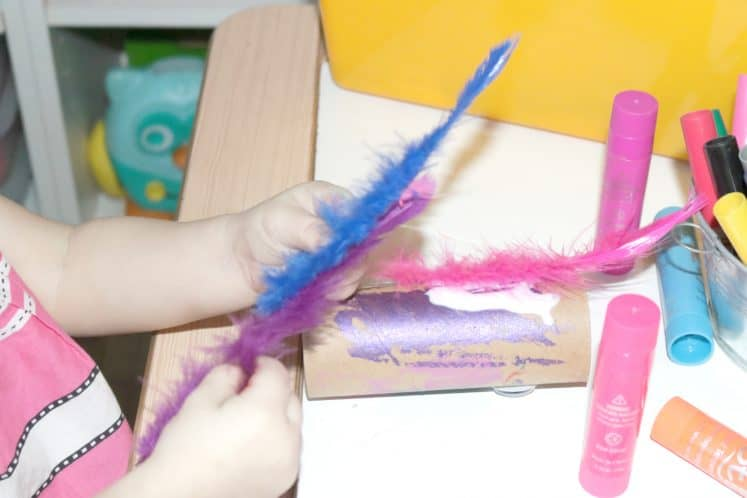 toddler exploring feathers