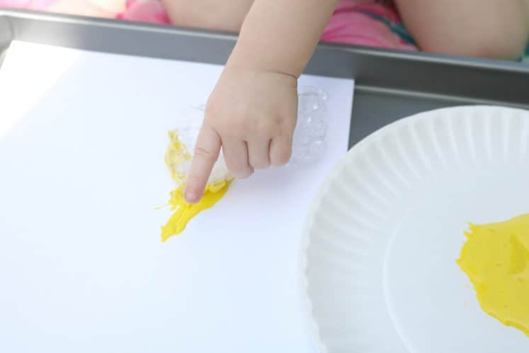 toddler using bubble wrap to put yellow paint onto white cardstock