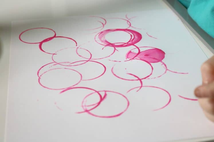 caterpillar art created by stamping pink circles on white cardstock using cardboard tubes