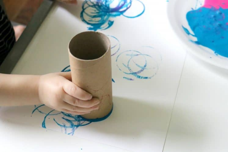 toddler using a cardboard tube to stamp circles on white cardstock