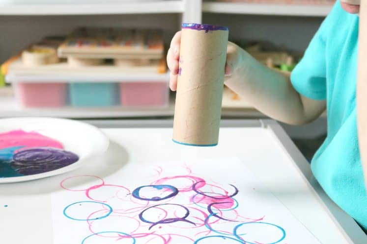 preschool caterpillar art made by stamping circles on cardstock using a cardboard tube