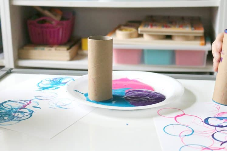 cardboard tube on paper plate with several colors of paint