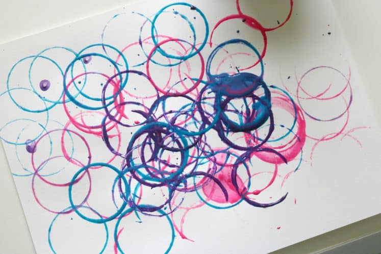preschooler's caterpillar painting art using cardboard tubes and paint to stamp circles on cardstock