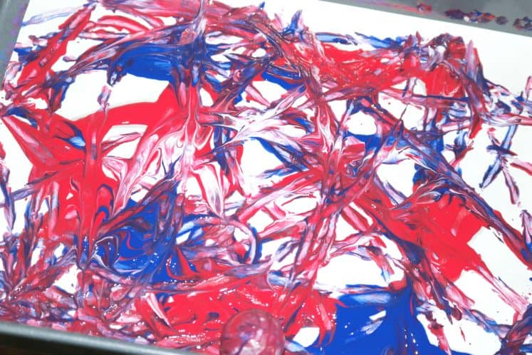 Patriotic Process Art created by putting cardstock and paint in a cake pan with small ball