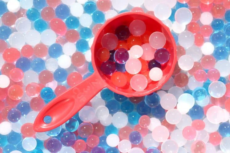 measuring cup with filled red, white and blue water beads