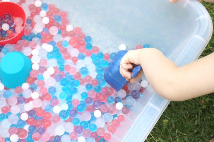 preschooler scooping water beads with a measuring cup