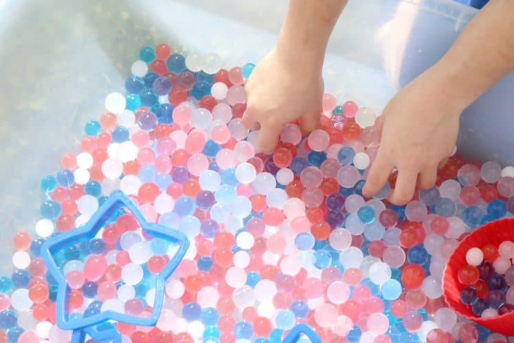 kindergartner using hands to scoop water beads from 4th of July sensory bin