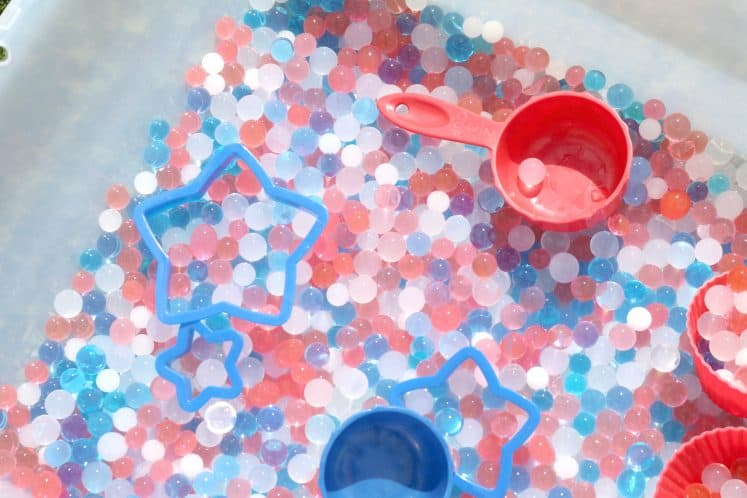measuring cups and cookie cutters in Independence Day sensory bin