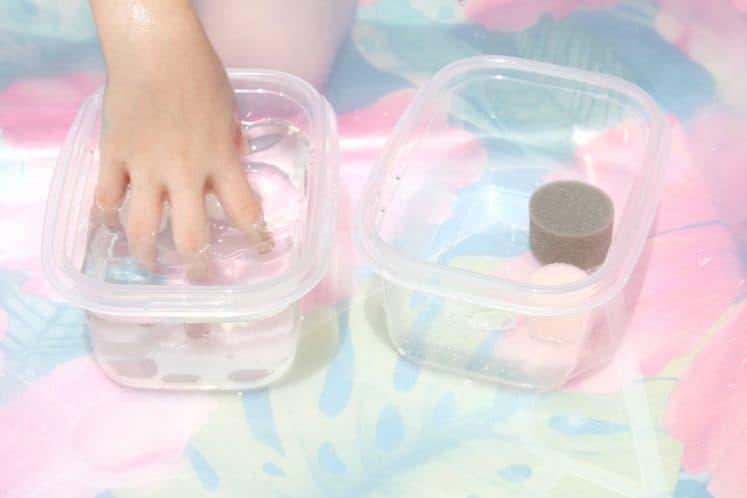 preschooler putting hand in bowl of water