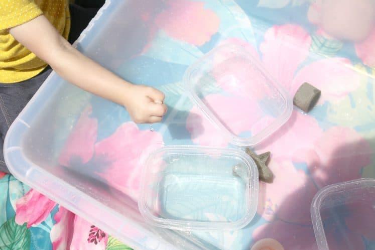 toddler squeezing sponge into sensory bin