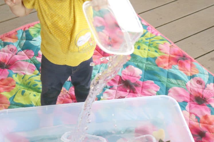 toddler pouring water from plastic container into large bin