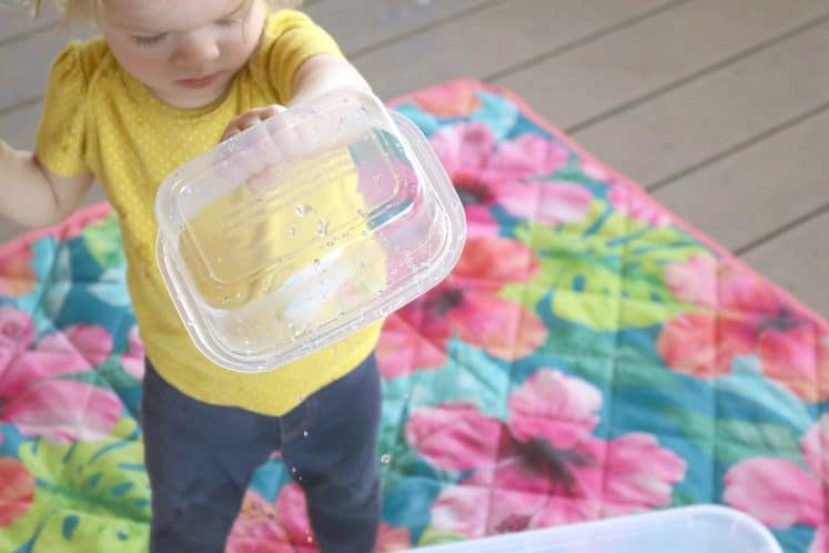 toddler holding empty container upside down