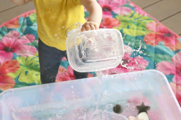 toddler dumping water from one container to another
