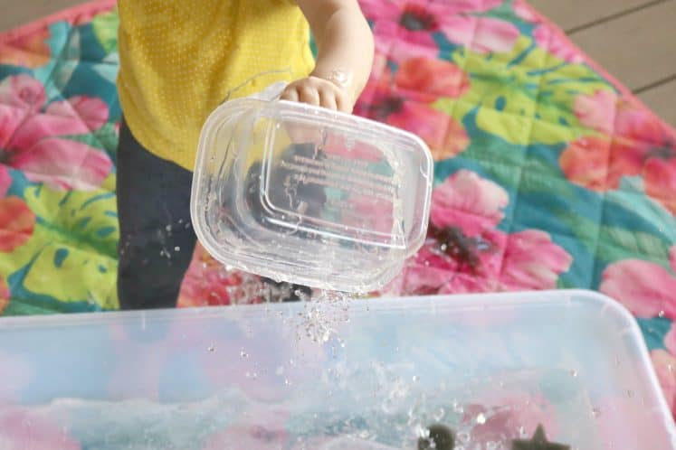toddler pouring water from clear container to large bin