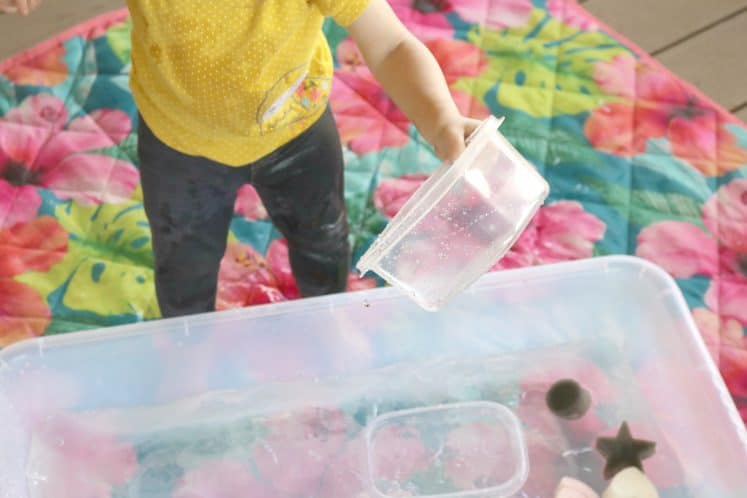 toddler holding small plastic container