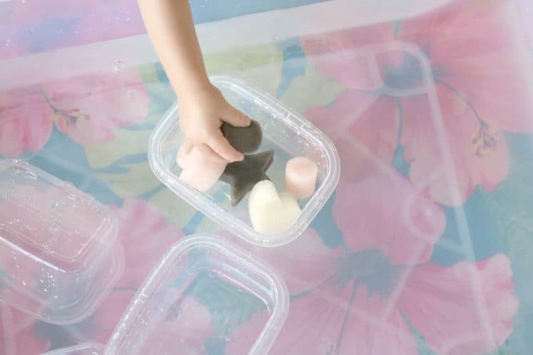 toddler filling plastic container with shape sponges