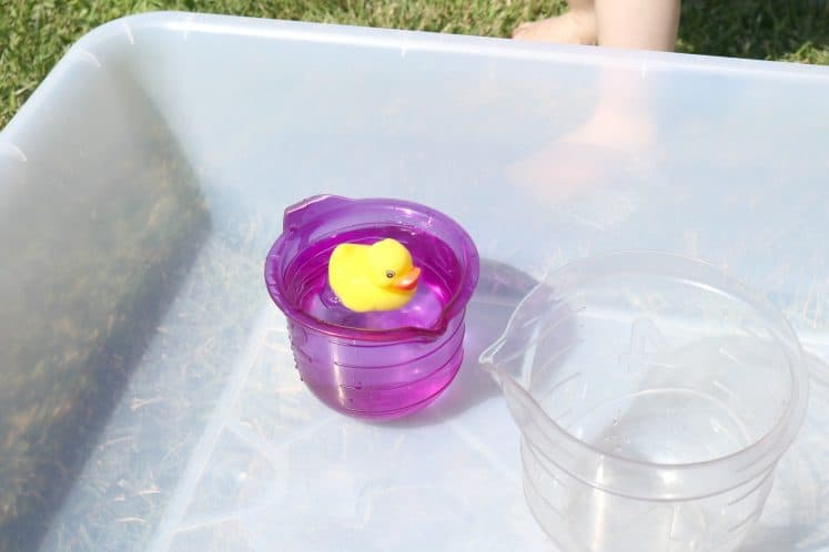 rubber duck floating in measuring cup filled with water