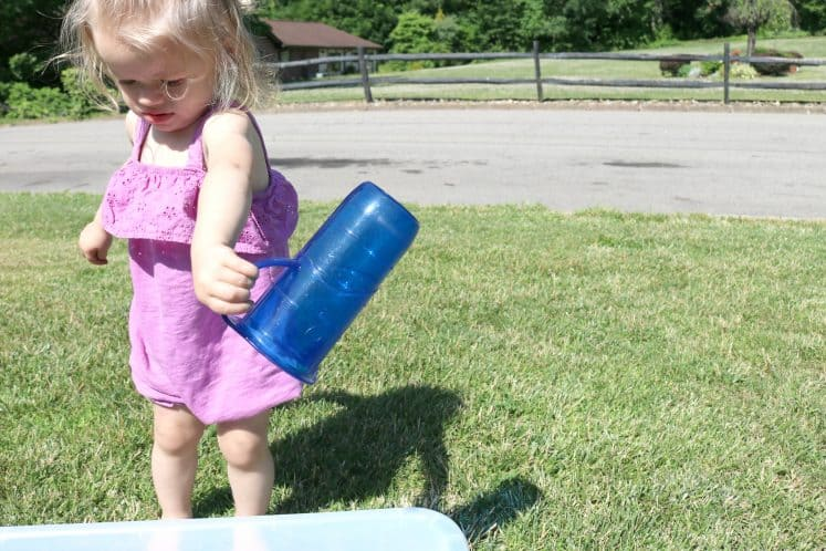 toddler pouring water from measuring cup into large plastic bin