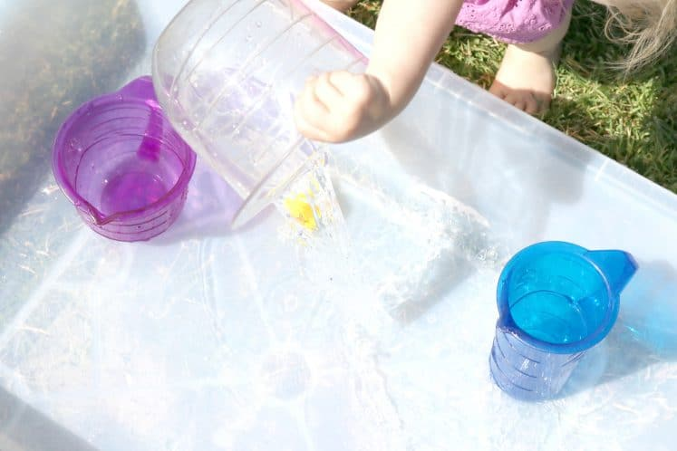 toddler pouring water from measuring cup into clear plastic bin