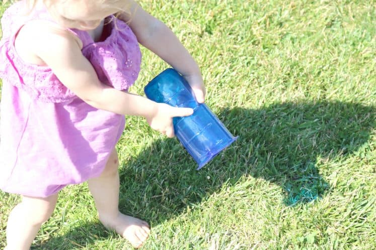 toddler using measuring cup to pour water onto grass