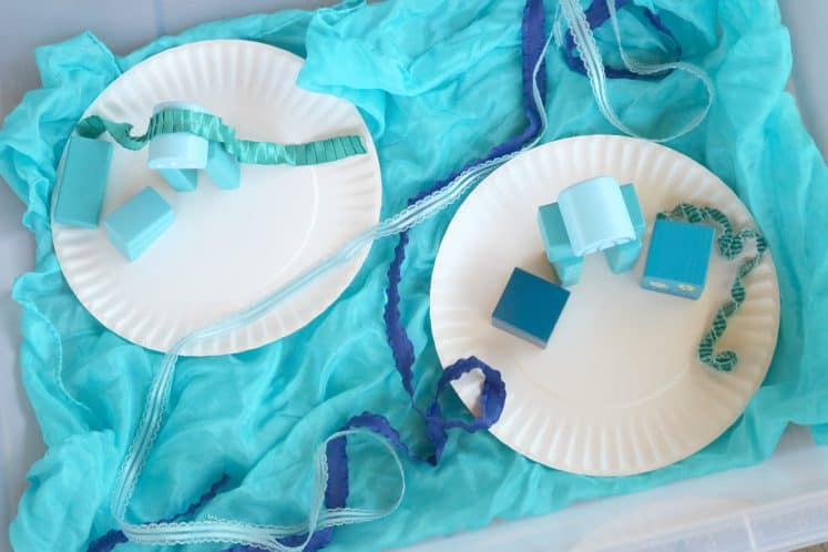 pretend play islands using blue play silk and paper plates with wooden blocks