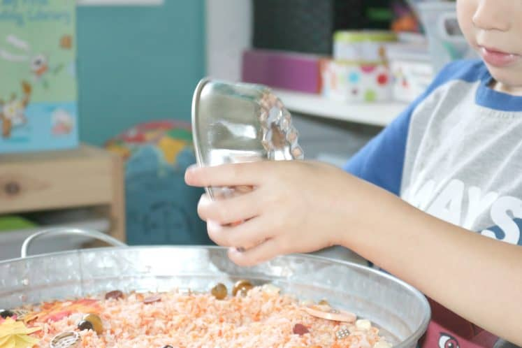 preschooler scooping dyed rice with small metal bowl