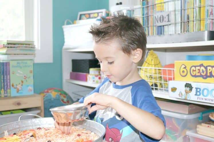 preschoolers filling up metal bowl with dyed rice