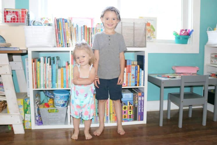 toddler and preschooler standing in front of bookcases