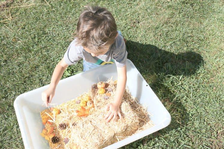 preschooler playing pretend with fall sensory bin