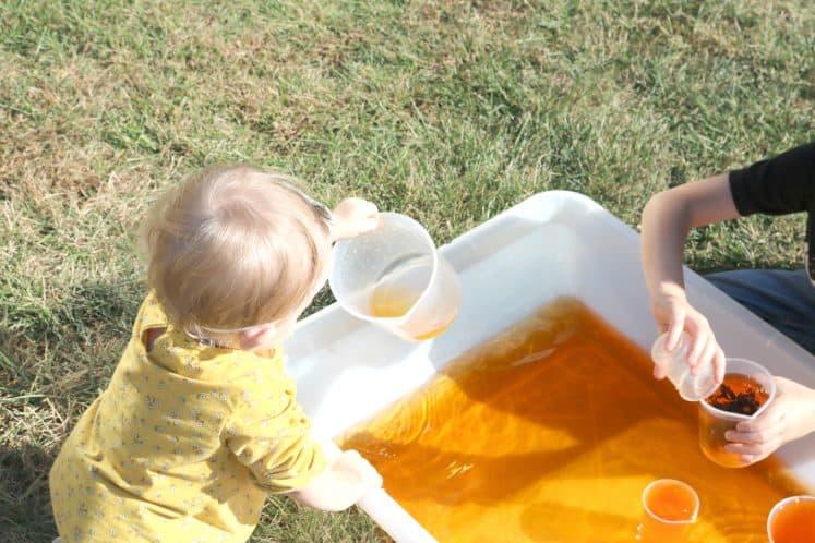 toddler holding empty plastic beaker