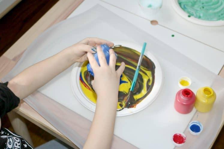 preschooler putting paint onto paper plate