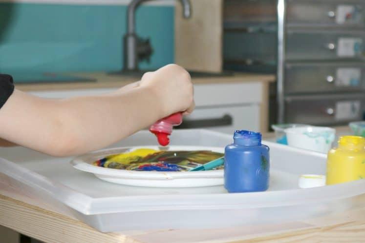 preschooler squeezing paint onto paper plate