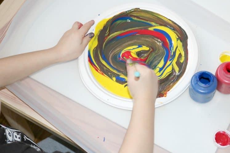 preschooler swirling paint on paper plate