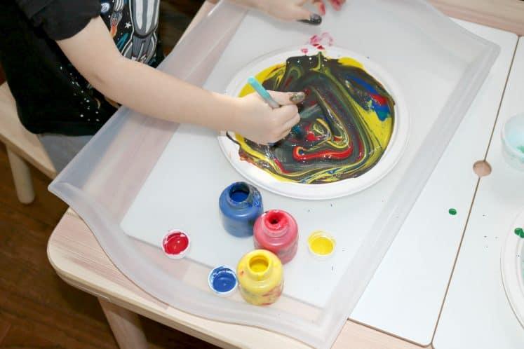 preschooler using paintbrush to swirl paint onto paper plate