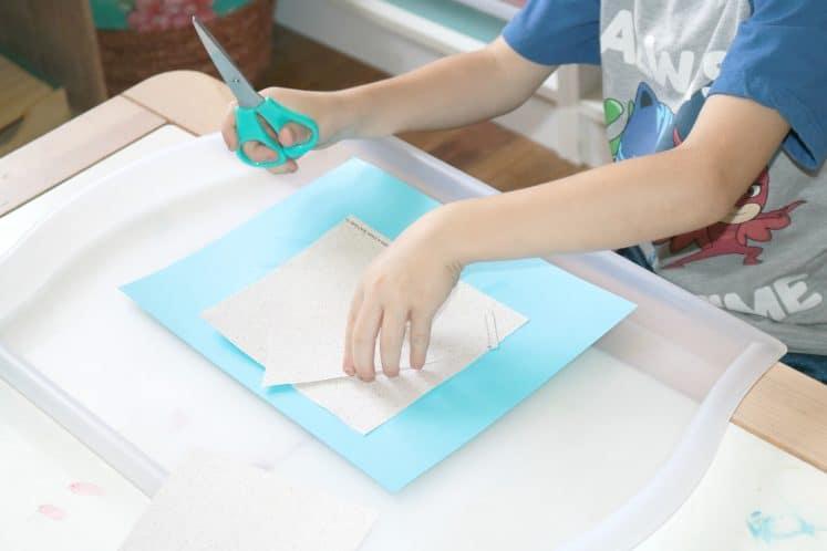 preschooler gluing large square onto cardstock