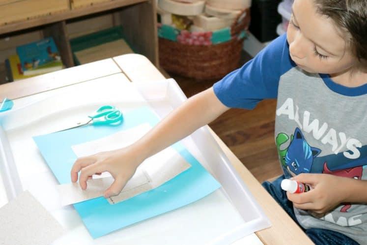 preschooler adding paper towers to sandcastle craft
