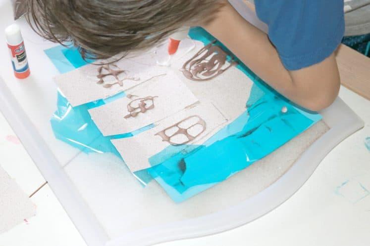 preschooler making doors and windows on sandcastle craft