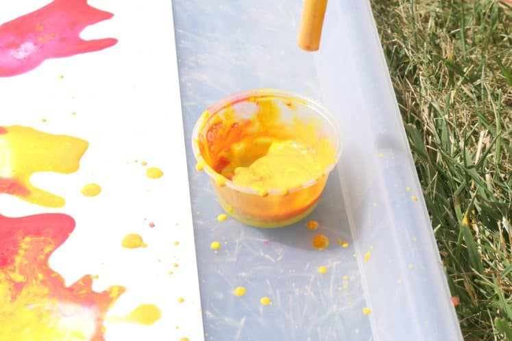kindergartner using a straw for blow painting process art