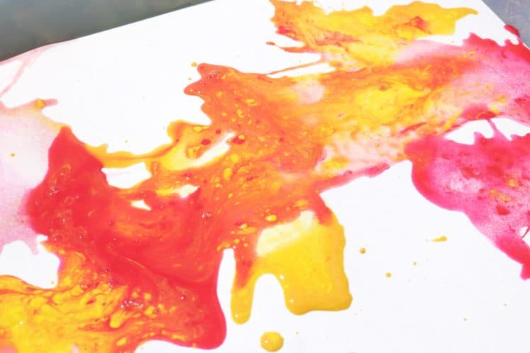 red and yellow paint splatters mixing to make orange paint