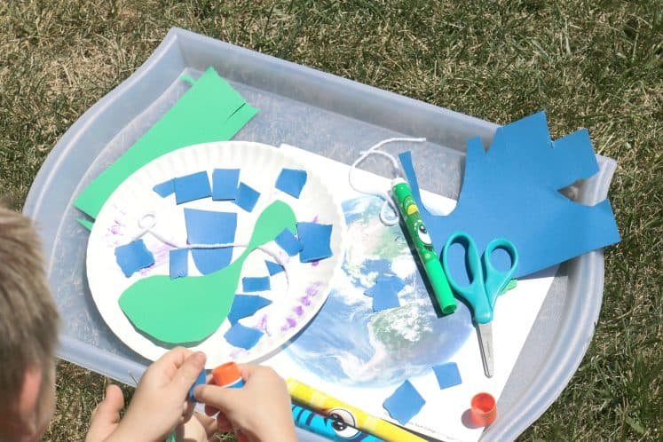 child creating Earth collage process art using paper plate