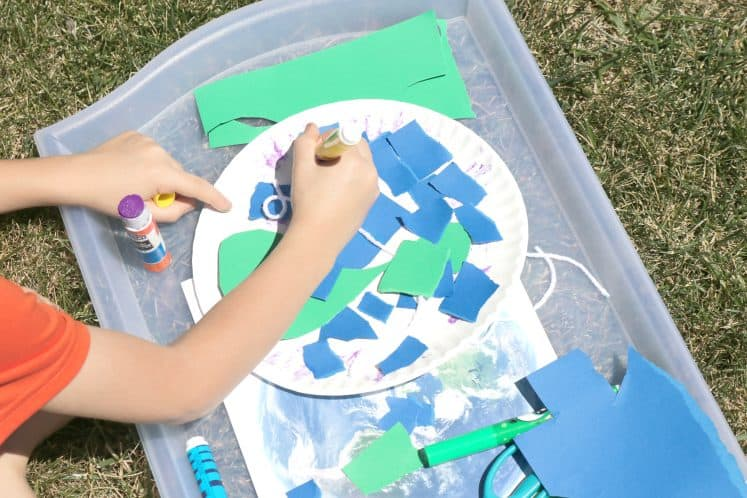 child coloring with markers to make Earth collage