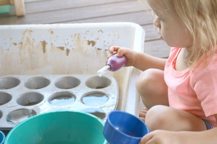 toddler playing with water sensory tray