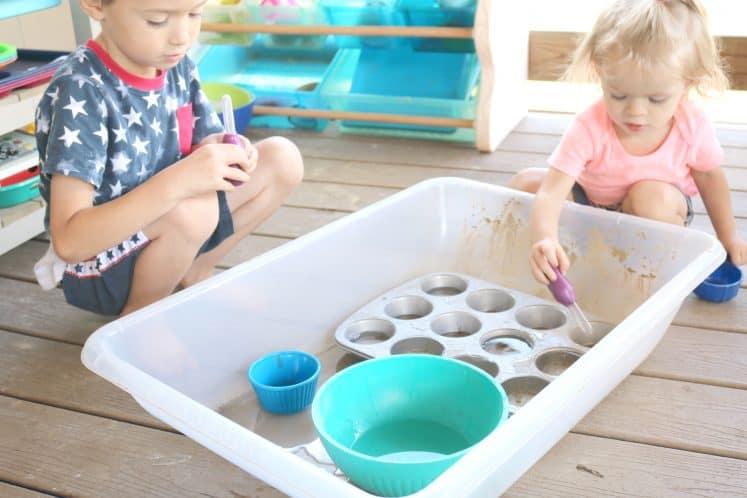 toddler and kindergartner exploring water sensory tray