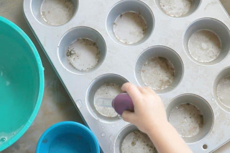 toddler dropping water into cupcake pan