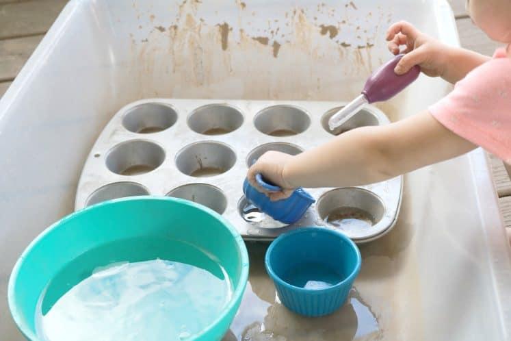 toddler dumping measuring cup into cupcake pan