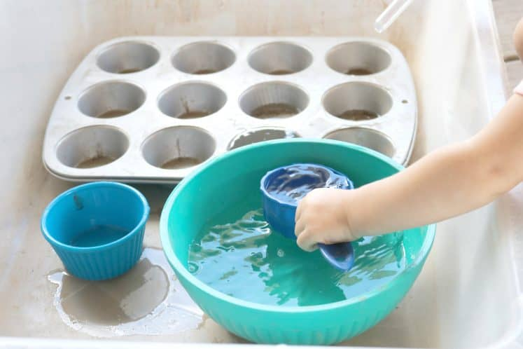 toddler scooping water with measuring cup