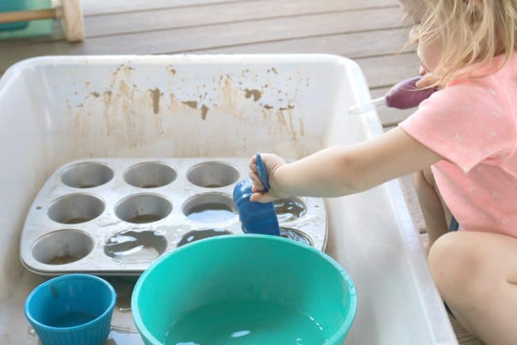 toddler dumping water into cupcake pan with measuring cup