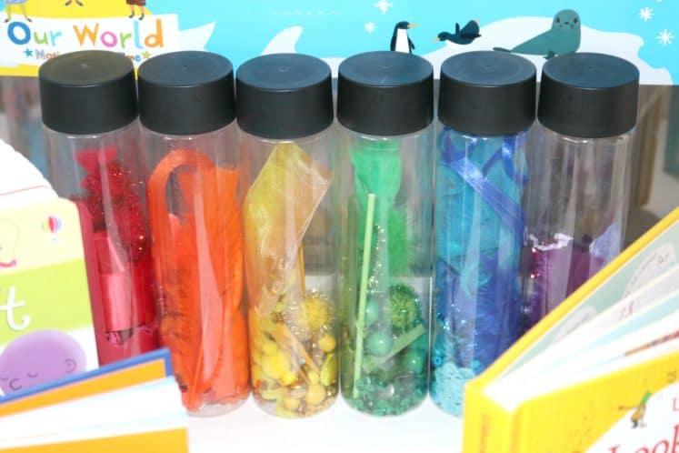 rainbow sensory bottles lined up on shelf